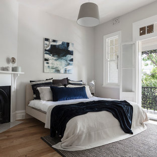 Idee per una grande camera matrimoniale classica con pareti grigie, pavimento in legno massello medio, camino ad angolo e cornice del camino in intonaco