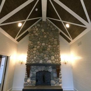 Ejemplo de habitación de invitados tradicional, de tamaño medio, con paredes blancas, chimenea tradicional, marco de chimenea de piedra y suelo de pizarra
