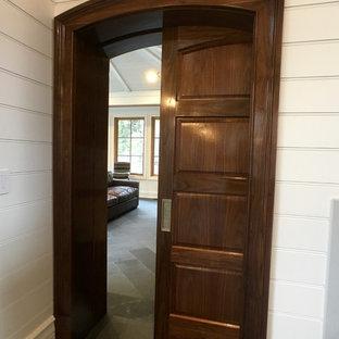 Modelo de dormitorio principal, clásico, extra grande, con paredes blancas, chimenea tradicional, marco de chimenea de piedra y suelo de pizarra