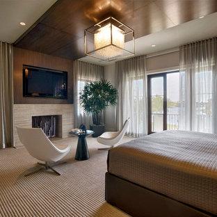 マイアミの大きいコンテンポラリースタイルのおしゃれな主寝室 (カーペット敷き、標準型暖炉、ベージュの壁) のインテリア