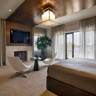 Inspiration for a large contemporary master bedroom in Miami with carpet, a standard fireplace and beige walls.