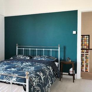 ロンドンの大きいヴィクトリアン調のおしゃれな主寝室 (マルチカラーの壁、カーペット敷き、標準型暖炉、木材の暖炉まわり、グレーの床)