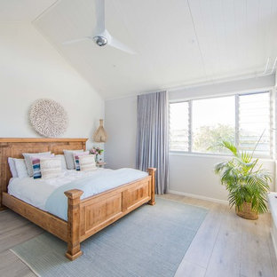 Design ideas for a large beach style master bedroom in Gold Coast - Tweed with white walls, light hardwood floors and grey floor.