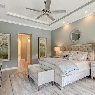 Ejemplo de dormitorio principal, tradicional renovado, grande, sin chimenea, con paredes verdes y suelo de madera clara