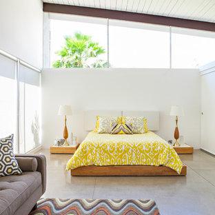 Стильный дизайн: спальня в стиле ретро с белыми стенами, бетонным полом и серым полом - последний тренд