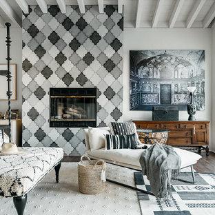 Foto de dormitorio mediterráneo con paredes blancas, suelo de madera oscura, chimenea tradicional, marco de chimenea de baldosas y/o azulejos y suelo marrón