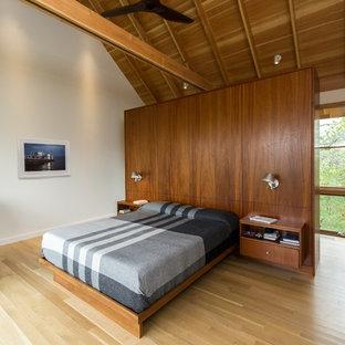 Imagen de dormitorio principal, minimalista, de tamaño medio, sin chimenea, con paredes blancas, suelo de madera clara y suelo beige