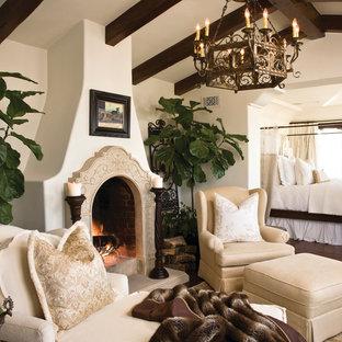 Foto di una grande camera matrimoniale mediterranea con camino classico, parquet scuro, cornice del camino in pietra, pavimento marrone e pareti bianche