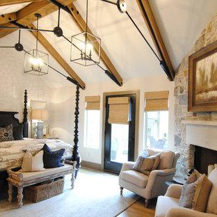 広いエクレクティックスタイルのおしゃれな主寝室 (白い壁、クッションフロア、コーナー設置型暖炉、石材の暖炉まわり、茶色い床) のレイアウト