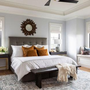 Ejemplo de dormitorio principal, tradicional renovado, sin chimenea, con paredes púrpuras y suelo de madera en tonos medios