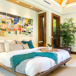 Exotisk inredning av ett stort huvudsovrum, med vita väggar, heltäckningsmatta och beiget golv
