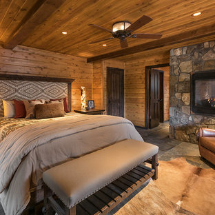 Diseño de dormitorio principal, rústico, grande, con suelo de pizarra, chimenea de doble cara, marco de chimenea de piedra, paredes marrones y suelo gris
