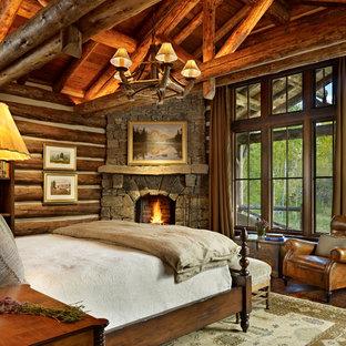 Foto de dormitorio rústico con chimenea de esquina y marco de chimenea de piedra