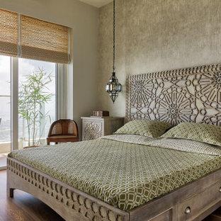 ムンバイの中くらいのトロピカルスタイルのおしゃれな主寝室 (グレーの壁、無垢フローリング、茶色い床) のレイアウト