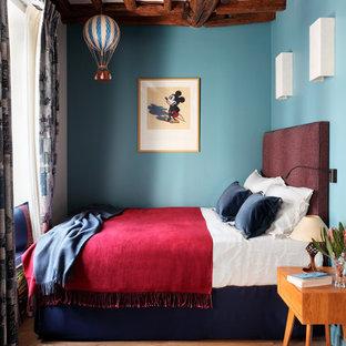 Inspiration för eklektiska sovrum, med blå väggar, mellanmörkt trägolv och brunt golv