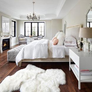 На фото: хозяйские спальни в классическом стиле с бежевыми стенами, паркетным полом среднего тона, стандартным камином, фасадом камина из дерева и коричневым полом