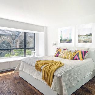Diseño de dormitorio principal, actual, con suelo de madera en tonos medios y paredes blancas