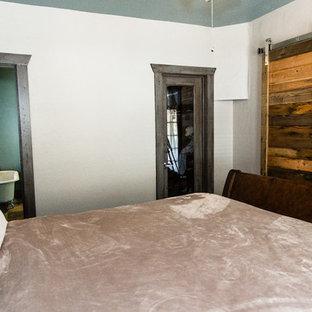 Imagen de dormitorio principal, rústico, pequeño, con paredes blancas, moqueta, estufa de leña, marco de chimenea de piedra y suelo marrón