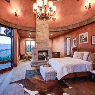 Modelo de dormitorio rústico con paredes rojas, suelo de madera oscura, chimenea de doble cara y marco de chimenea de piedra