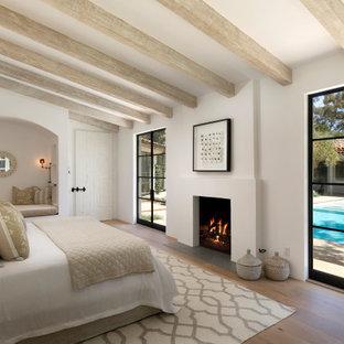 Idéer för ett medelhavsstil sovrum, med vita väggar, mellanmörkt trägolv, en standard öppen spis och brunt golv