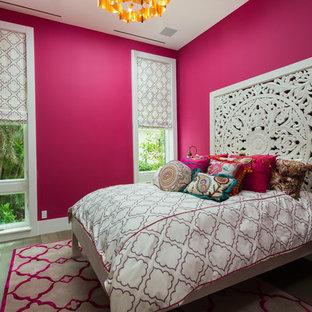 Modelo de habitación de invitados actual con paredes rosas, suelo de madera en tonos medios y suelo marrón