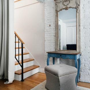 Imagen de dormitorio principal, campestre, pequeño, con paredes multicolor, suelo de madera en tonos medios, chimenea tradicional y marco de chimenea de ladrillo
