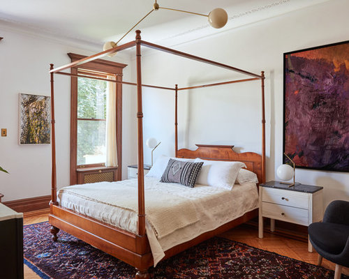 Example Of A Classic Medium Tone Wood Floor And Brown Floor Bedroom Design  In New York