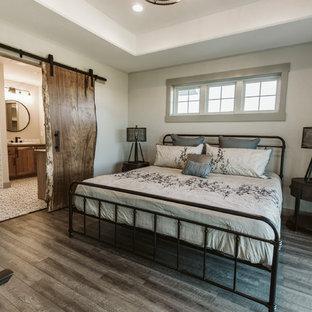 Imagen de dormitorio principal, de estilo de casa de campo, de tamaño medio, con paredes blancas, suelo vinílico y suelo marrón