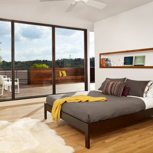 Example of a minimalist light wood floor and yellow floor bedroom design in Austin with white walls