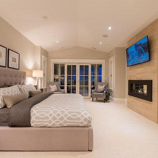 Идея дизайна: большая хозяйская спальня в стиле современная классика с белыми стенами, ковровым покрытием, двусторонним камином и фасадом камина из камня