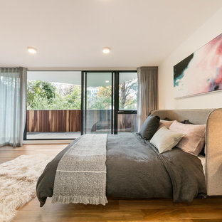 Contemporary master bedroom in Melbourne with white walls, medium hardwood floors and brown floor.
