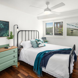 Photo of a tropical bedroom in Other with white walls, dark hardwood floors and brown floor.