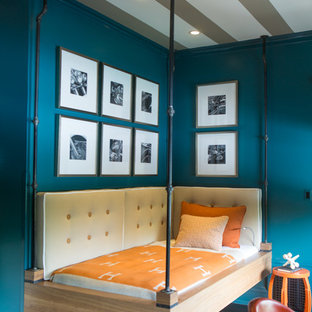 Mid-sized industrial guest bedroom in Orange County with blue walls, dark hardwood floors, no fireplace and brown floor.
