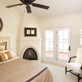 Modelo de dormitorio principal, mediterráneo, de tamaño medio, con paredes blancas, chimenea de esquina, moqueta, marco de chimenea de yeso y suelo beige