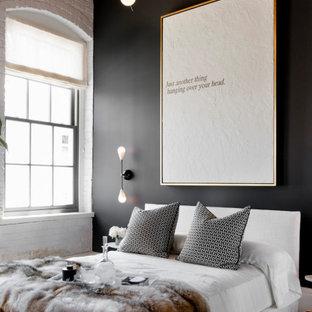 Bild på ett mellanstort industriellt sovrum, med svarta väggar, mellanmörkt trägolv och brunt golv
