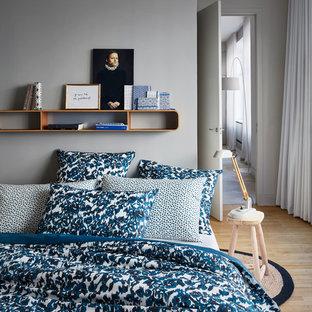 Cette photo montre une petite chambre parentale scandinave avec un sol en bois clair et un mur gris.