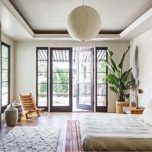 Diseño de dormitorio principal, actual, extra grande, con paredes blancas, suelo de madera clara, marco de chimenea de hormigón y chimenea tradicional