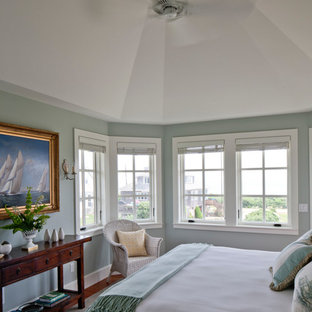 Photo of a large beach style master bedroom in Boston with green walls, medium hardwood floors, no fireplace and brown floor.