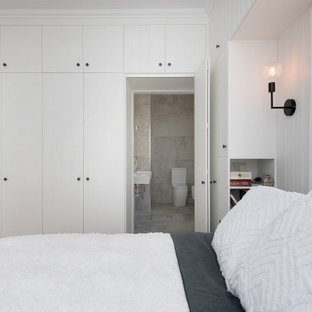 Photo of a mid-sized traditional master bedroom in Brisbane with white walls, light hardwood floors, yellow floor, wood and panelled walls.
