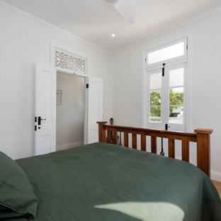 Esempio di una camera degli ospiti tradizionale di medie dimensioni con pareti bianche, parquet chiaro, pavimento giallo, soffitto in legno e pannellatura
