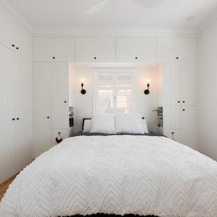 Ejemplo de dormitorio principal, madera y panelado, tradicional, de tamaño medio, panelado, con paredes blancas, suelo de madera clara, suelo amarillo y panelado