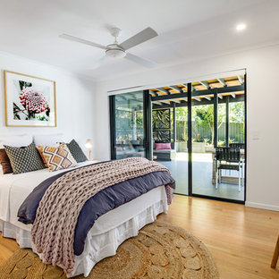 Contemporary bedroom in Sunshine Coast with white walls, medium hardwood floors and brown floor.
