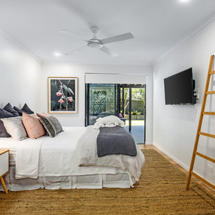 Design ideas for a large contemporary guest bedroom in Sunshine Coast with white walls, medium hardwood floors and brown floor.
