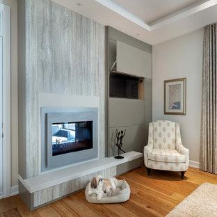 オタワの広いコンテンポラリースタイルのおしゃれな主寝室 (グレーの壁、無垢フローリング、両方向型暖炉、漆喰の暖炉まわり、茶色い床) のレイアウト