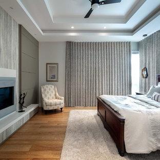 オタワの大きいコンテンポラリースタイルのおしゃれな主寝室 (グレーの壁、無垢フローリング、両方向型暖炉、漆喰の暖炉まわり、茶色い床) のレイアウト