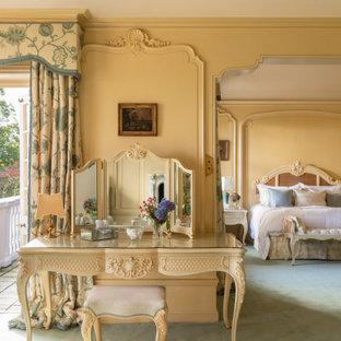 На фото: большая хозяйская спальня в классическом стиле с желтыми стенами, ковровым покрытием и зеленым полом с