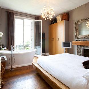 Foto de dormitorio principal, minimalista, de tamaño medio, con paredes grises, suelo de madera en tonos medios, chimenea tradicional y marco de chimenea de ladrillo