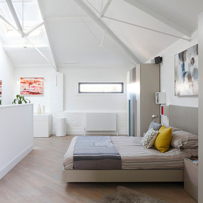 Example of a mid-sized trendy master light wood floor and beige floor bedroom design in London with white walls
