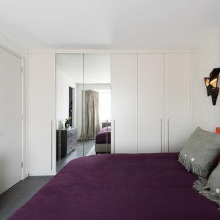 Modelo de dormitorio actual con paredes blancas, suelo de madera oscura y suelo negro