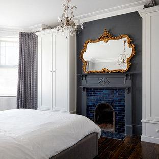 Inredning av ett modernt mellanstort huvudsovrum, med grå väggar, mörkt trägolv, en standard öppen spis och en spiselkrans i trä